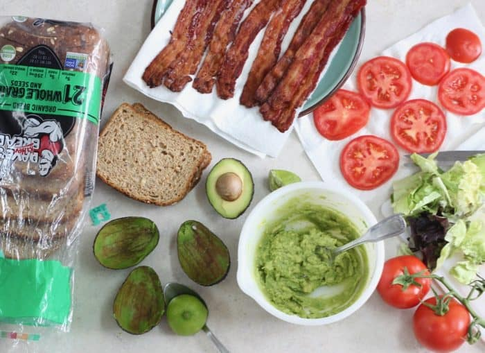 mashed avocado, bread, bacon, sliced tomatoes