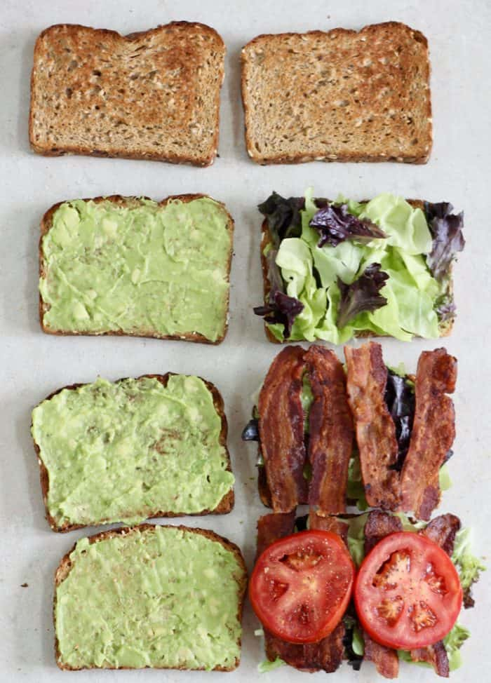 assembly line of making an avocado blt with bread, avocado, lettuce, bacon, and tomato