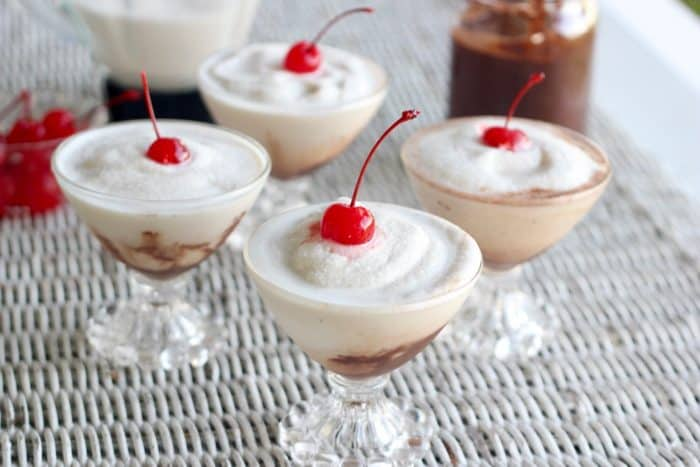 four glasses of bushwackers with cherries on top, chocolate sauce, cherries