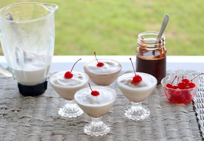 four frozen bushwackers with cherries on top, a pitcher of bushwackers, cherries and chocolate sauce