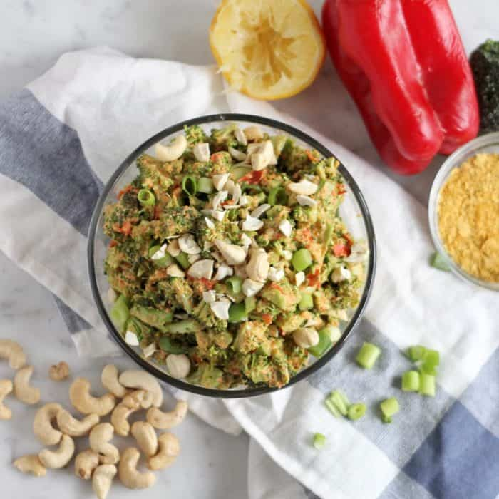 vegan broccoli salad with cashews, green onions, nutritional yeast, red bell pepper, and lemon