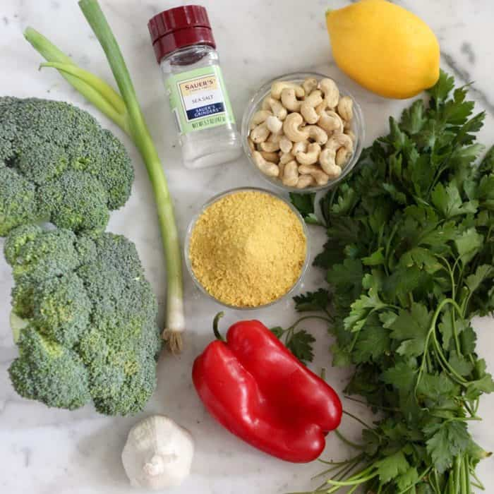 ingredients for vegan broccoli salad of fresh broccoli, green onion, garlic, salt, nutritional yeast, red bell pepper, cashews, lemon, and parsley