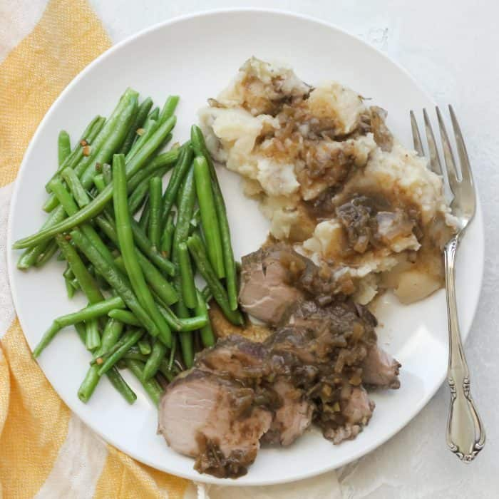 green beans, crock pot pork tenderloin with gravy, mashed potatoes and fork on white plate with white and yellow towel