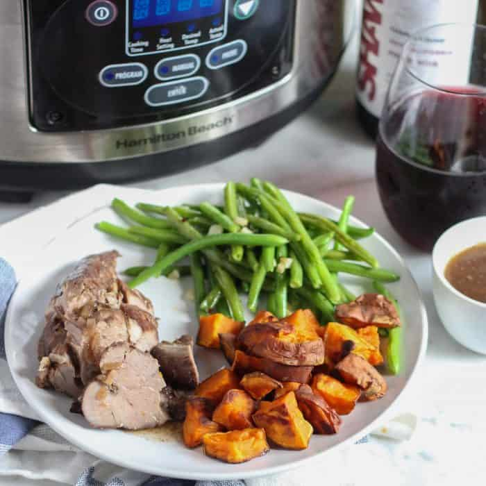 a white plate with crock pot pork tenderloin with roasted sweet potatoes and sautéed green beans with a bowl of gravy, wine and slow cooker in background