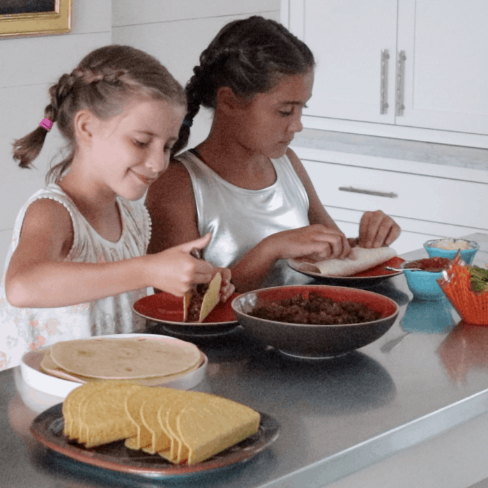 two young girls preparing tacos