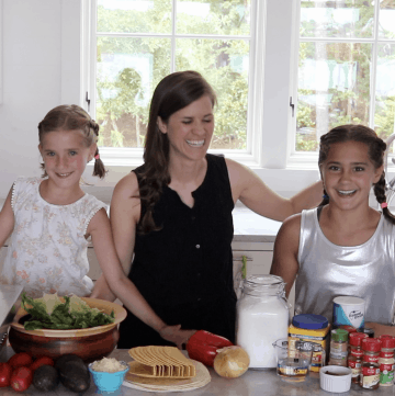 Two girls and an adult cooking tacos