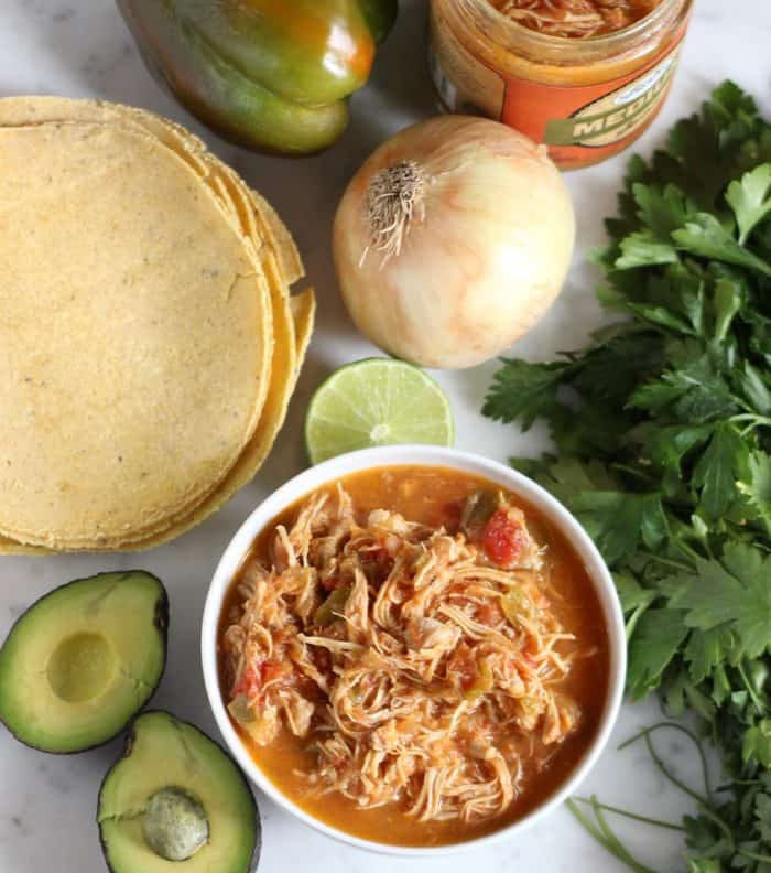 bowl of salsa chicken with tortillas, avocados, lime, onion, green bell pepper, jar of salsa, and parsley