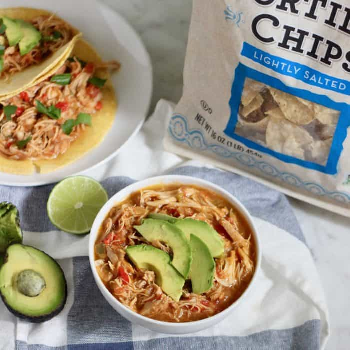 bowl of salsa chicken with sliced avocados, bag of tortilla chips, tacos on the side