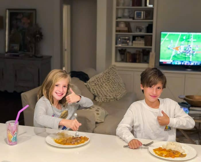 girl and boy eating lamb curry with football game on tv