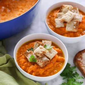 bowls of roasted carrot soup topped with parsley and cheese croutons