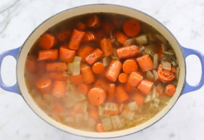 soup pot with roasted carrots, spices, and onions
