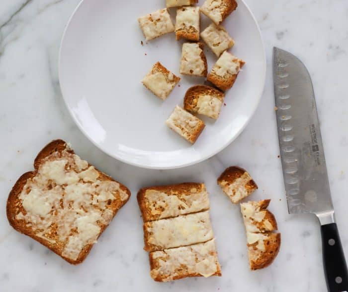 slicing cheese toast to make parmesan croutons