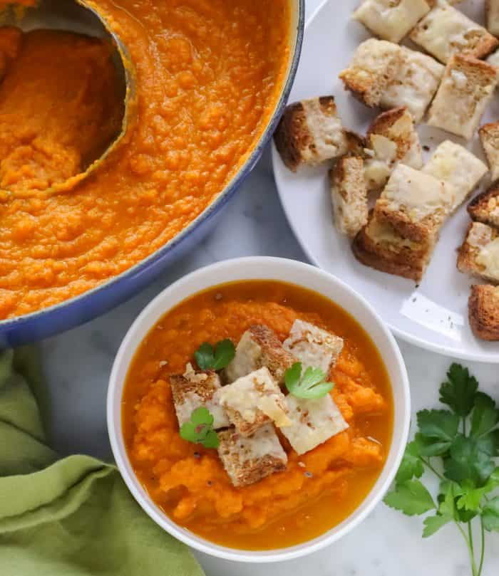bowl of roasted carrot soup topped with cheese croutons