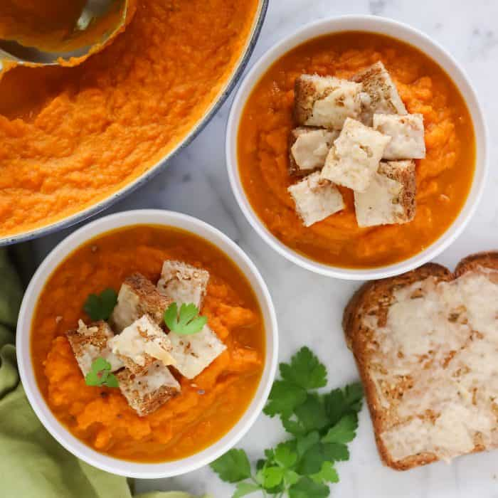 bowls of roasted carrot soup and cheese toast