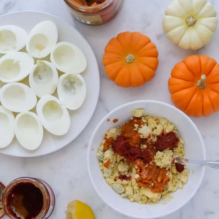 plate of egg whites with a bowl of yolks, pumpkin, and harissa paste to make pumpkin deviled eggs