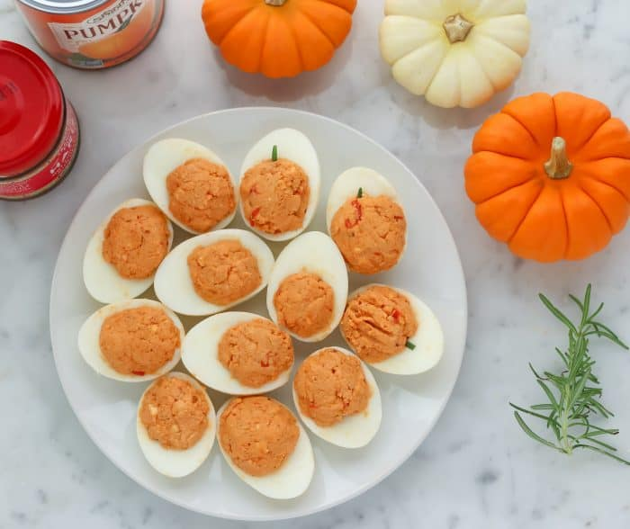 plate of deviled eggs with mini pumpkins