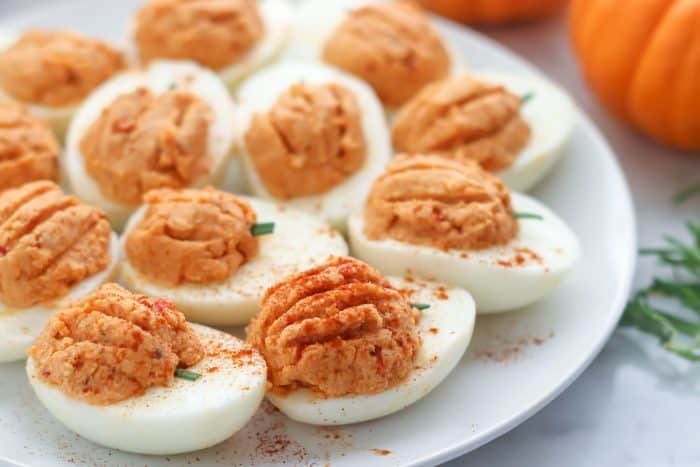 close up photo of pumpkin deviled eggs being sprinkled with paprika
