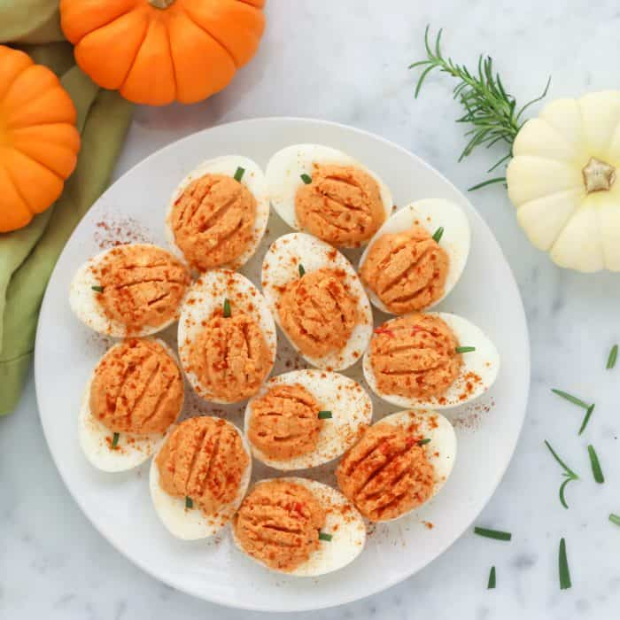 plate of pumpkin deviled eggs with rosemary and pumpkins