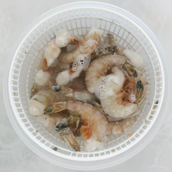 plastic bowl with frozen shrimp thawing