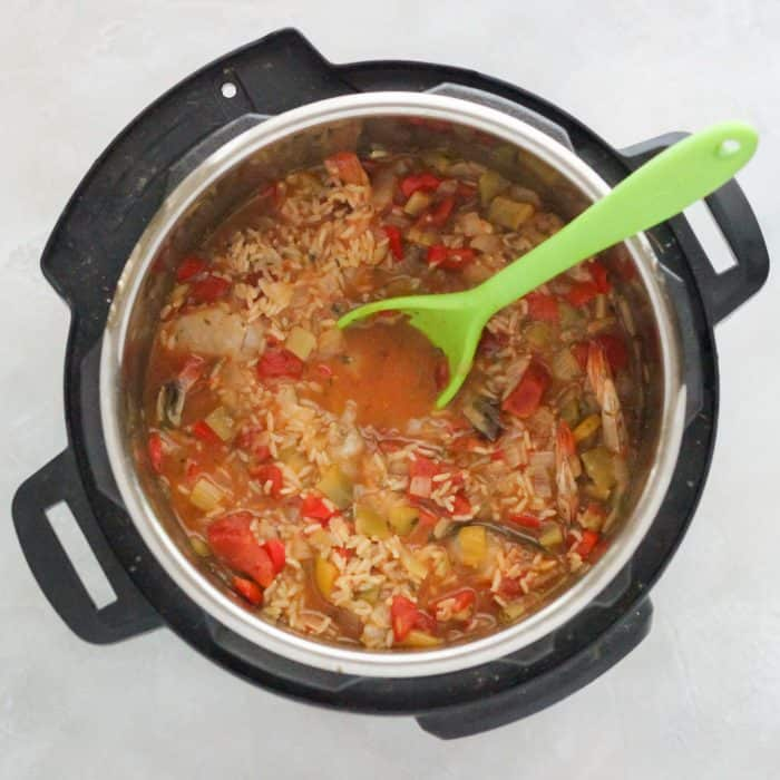 instant pot with cooked jambalaya and green spoon