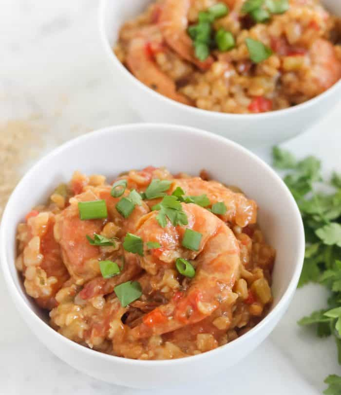 bowl of shrimp jambalaya with parsley and green onions, uncooked rice