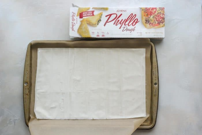 parchment lined baking sheet with phyllo dough and box of dough