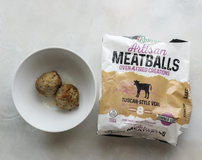 white bowl with microwaved meatballs and bag of frozen meatballs