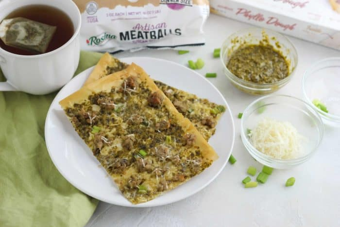white plate of flatbreads with green onions sprinkled and meatballs, pesto, parmesan
