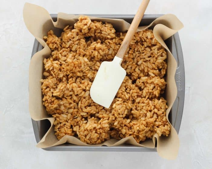 rice crispy treats being pressed into baking dish with parchment paper by a spatula