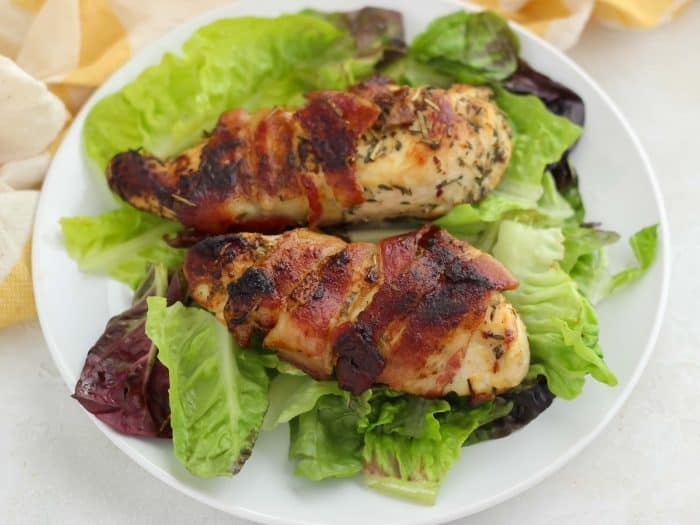 bacon wrapped chicken breast on top of lettuce