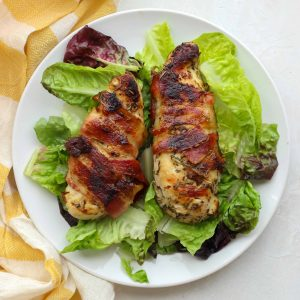 two pieces of bacon wrapped chicken breast over lettuce