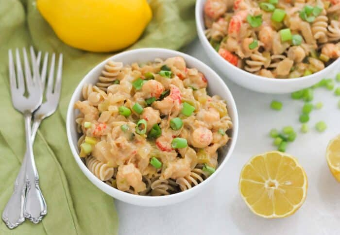 two bowls of crawfish pasta with forks, lemon, green onions