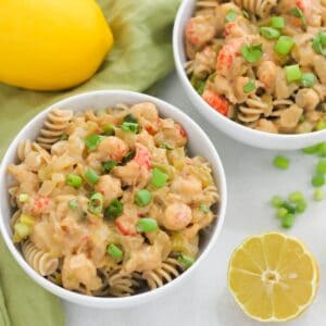 bowls of crawfish pasta with parsley, green onions, and lemon