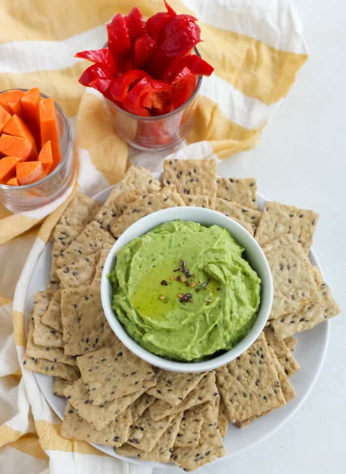 yellow and white striped towel with sliced carrots and bell peppers and a plate of crackers with bowl of spinach avocado hummus