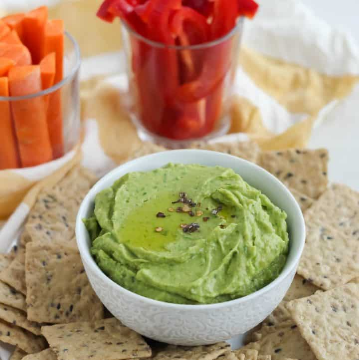 white bowl of spinach hummus surrounded by crackers, sliced veggies