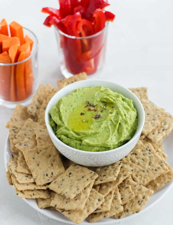 plate of crackers with white bowl of avocado spinach hummus, glasses full of sliced carrots and bell peppers