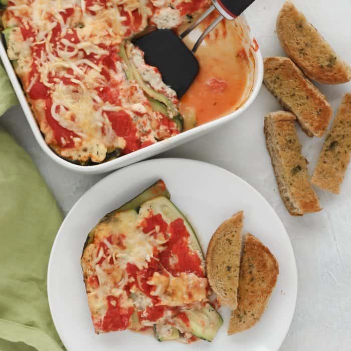 zucchini lasagna on white plate with garlic bread and casserole dish with spatula