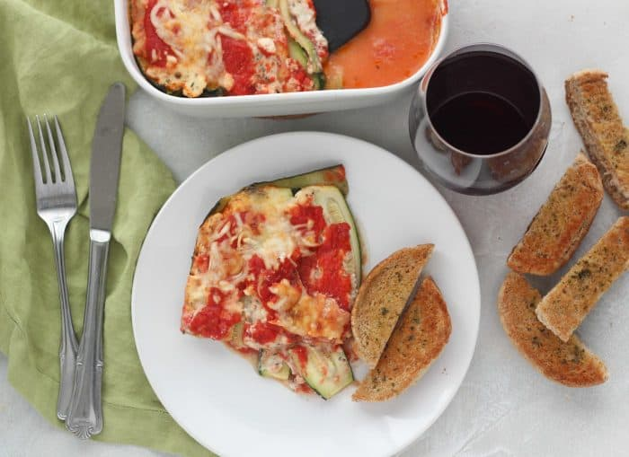zucchini lasagna on white plate with garlic bread and casserole dish, red wine