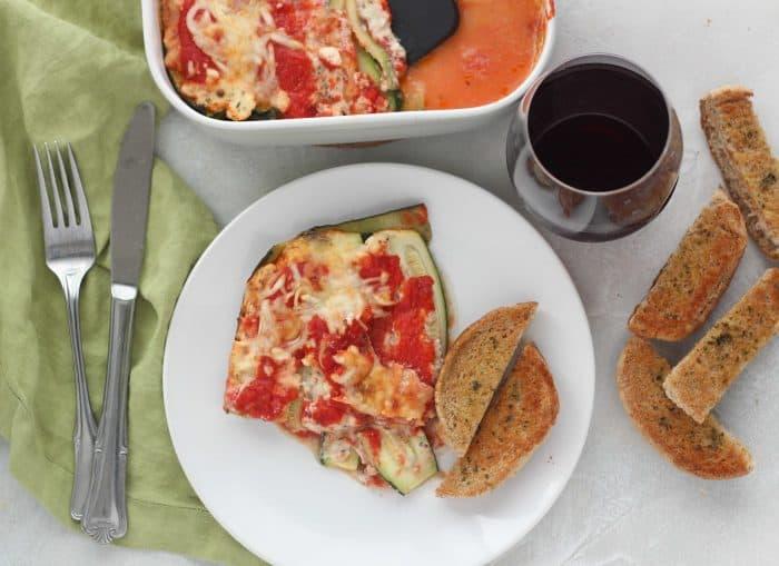 zucchini lasagna on white plate with garlic bread and casserole dish, red wine