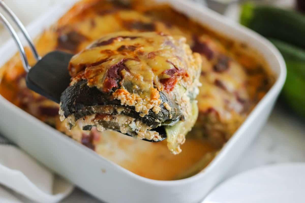 black spatula holding a slice of zucchini lasagna with casserole dish and fresh zucchini in background