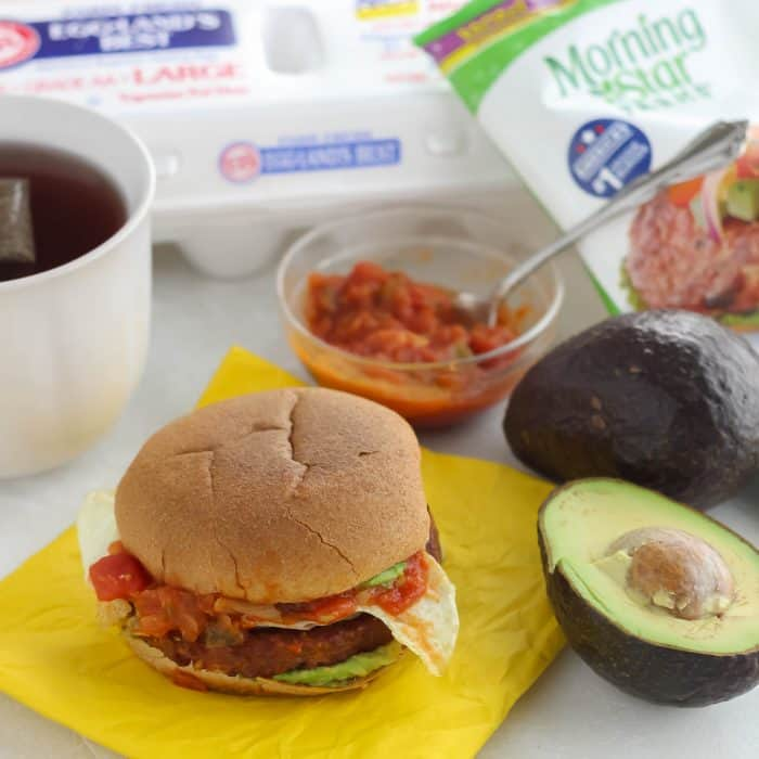 breakfast burger on yellow napkin, avocado, tea, salsa, egg carton, veggie burger wrapper
