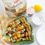 chicken nugget vegetable kabobs on a plate of green leaf lettuce, dipping sauce, lemon, yogurt, bag of frozen chicken nuggets
