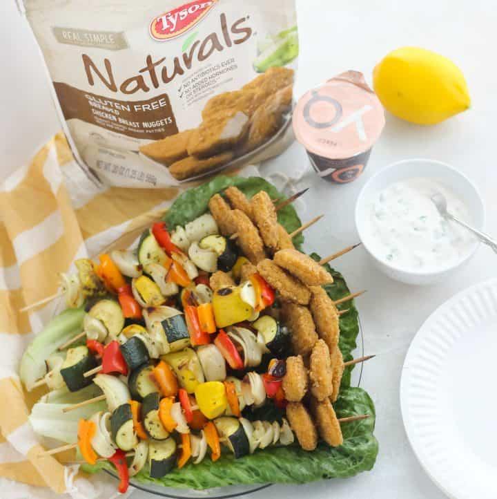 chicken nugget vegetable kabobs on a plate of green leaf lettuce, dipping sauce, lemon, yogurt, bag of frozen chicken nuggets