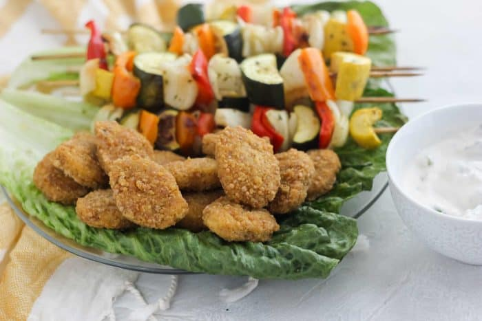 chicken nuggets and vegetable kabobs on green leaf lettuce
