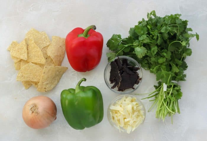 tortilla chips, onion, red bell pepper, green bell pepper, bowl of beef jerky, bowl of shredded cheddar cheese, cilantro