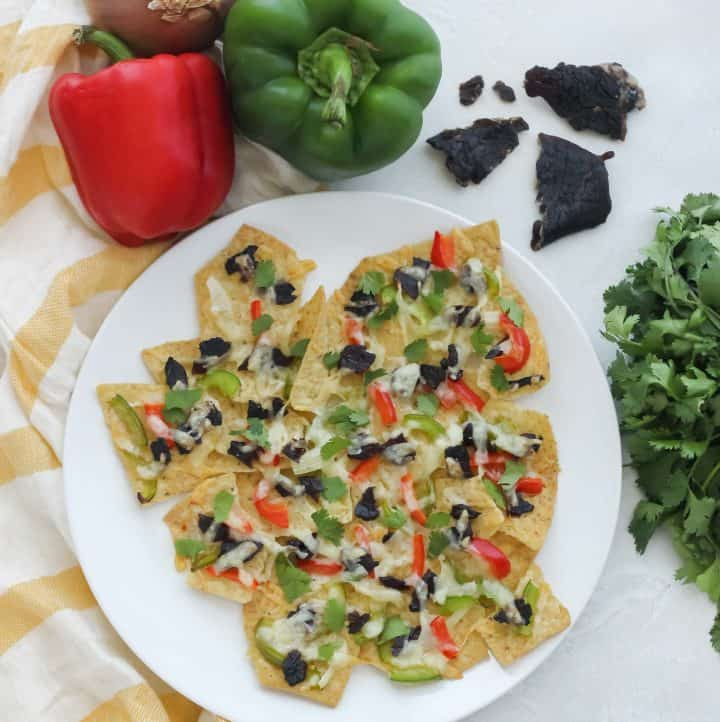 white plate with beef jerky nachos, red and green bell pepper, beef jerky, cilantro