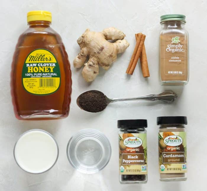 honey, milk, fresh ginger, spoonful of black tea, water, cinnamon sticks, cardamom, ground cinnamon, black peppercorns