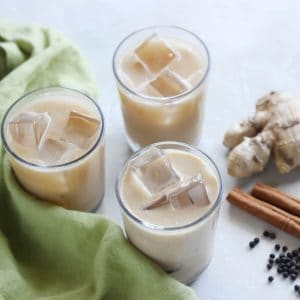 three small glasses of iced chai lattes with fresh ginger, cinnamon sticks, black peppercorns