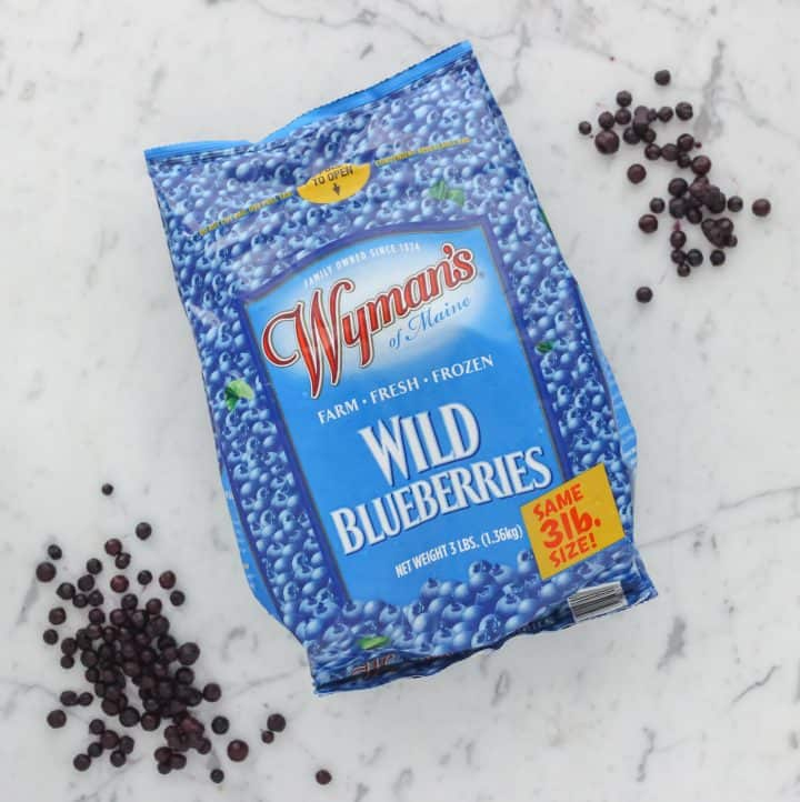 bag of frozen Wyman's Wild Blueberries on marble counter with some blueberries scattered around