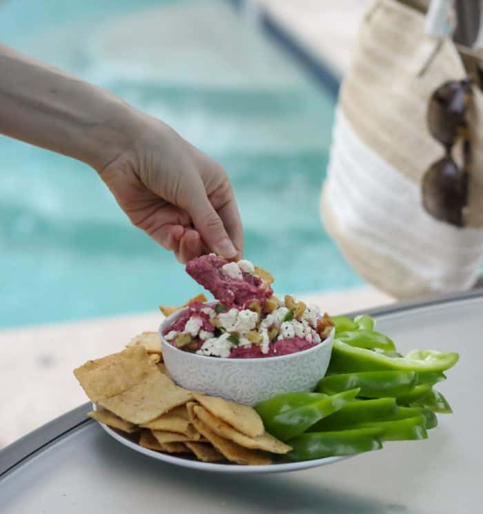 hand dipping a pita chip into beet hummus with feta on top, plate with pita chips and peppers on a table near a pool